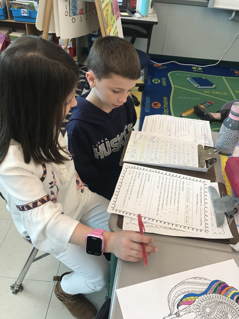 Second graders work together on writing opinion pieces.