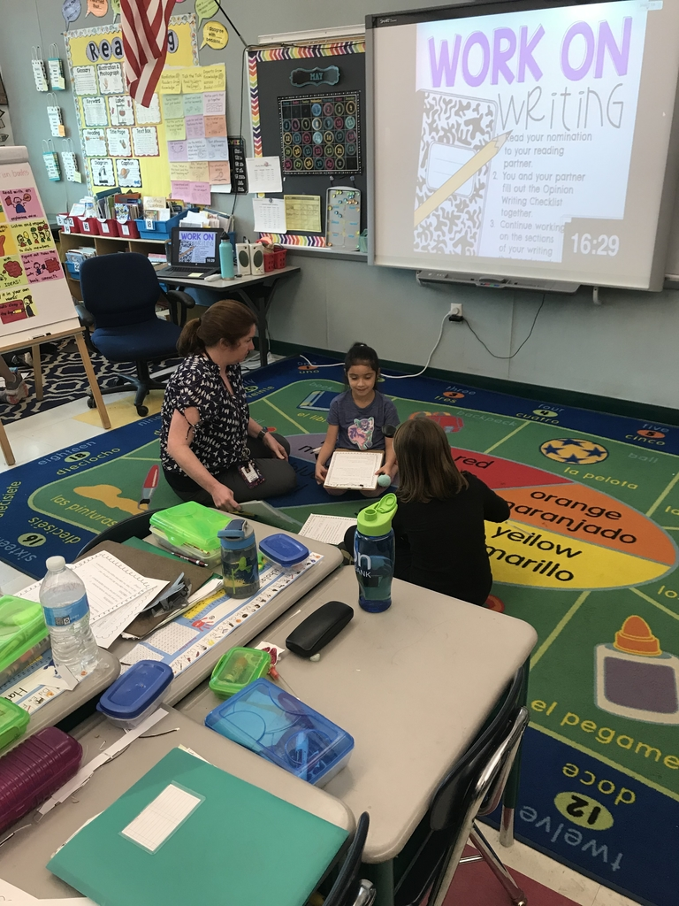 Mrs. Metcalfe works with two students during writing.